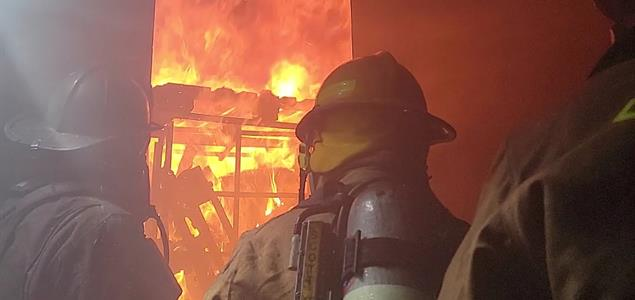 DOC Fire Emergency Response Team Members stand before a fire