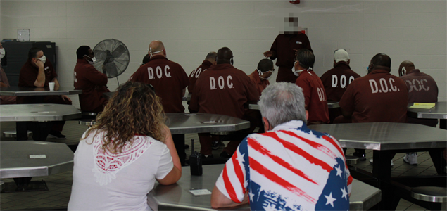 Two Camp Hill employees and a group of inmates watch an inmate speak to the group