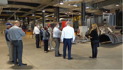 A group of people visit the vehicle restoration plant