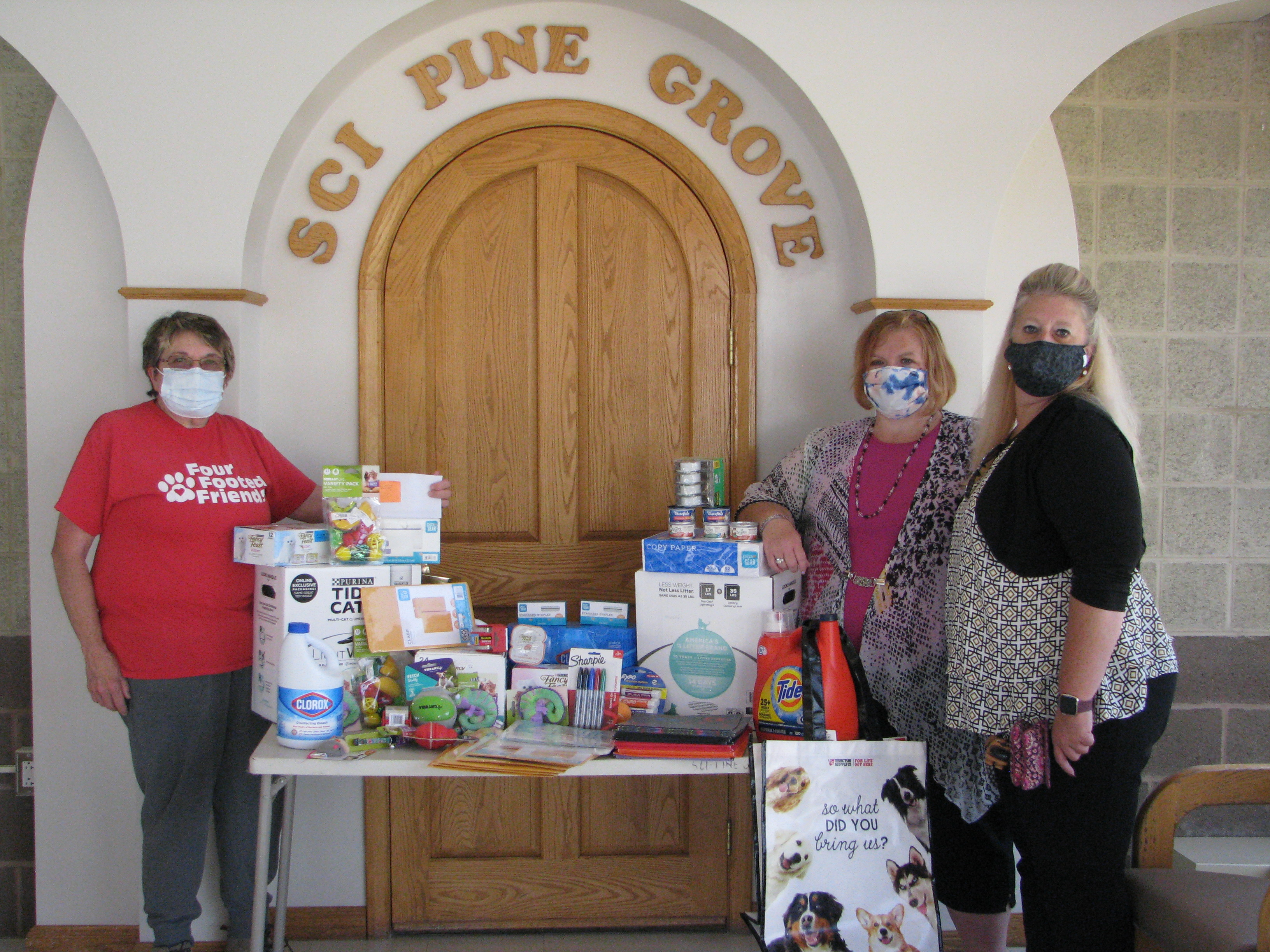 Three people stand by a table of donations