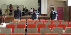 Three graduates stand at the front of the auditorium listening to a speech during their graduation ceremony